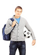 Young male student with school bag holding a football