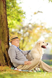 Senior gentleman and dog sitting on ground and posing in a park