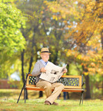 Senior man seated on a bench reading a newspaper in a park