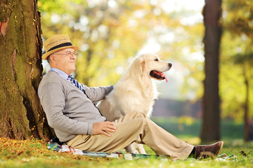 Senior gentleman and his dog sitting on ground in a park