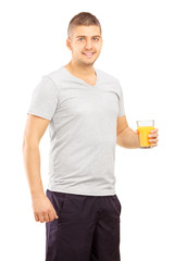 Smiling young sportsman posing with a glass of juice