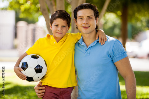 Happy father and son playing soccer