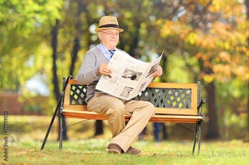 Senior gentleman seated on a bench reading a newspaper
