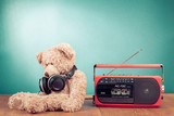 Retro toy Teddy Bear with headphones and radio recorder