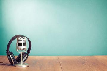 Retro style microphone, headphones in front aquamarine wall