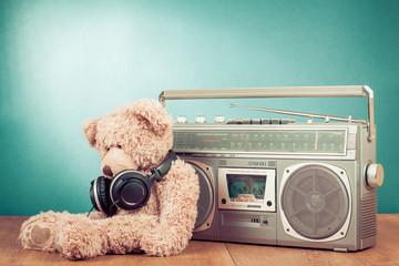 Retro Teddy Bear with headphones near radio cassette recorder