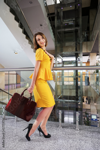 Happy young business woman in office interior