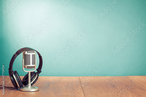 Retro style microphone, headphones in front aquamarine wall