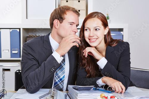 Geschäftsmann flüstert Kollegin ein Geheimnis zu