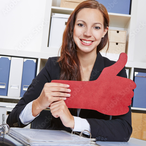 Frau im Büro hält roten Daumen hoch
