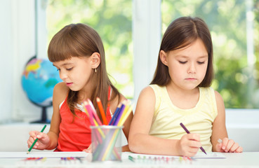 Little girls are drawing using pencils