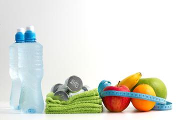 Hantle fitness z owocami i wodą na białym tle.