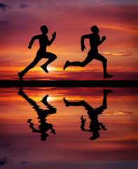 Silhouettes of two runners on sunset fiery background.