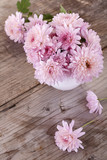 magenta flowers in a white vase on a wooden board