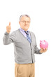 Smiling mature gentleman holding a piggy bank giving thumb up