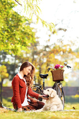 Beautiful female sitting on a grass and looking at her dog