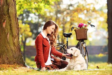 Beautiful female sitting on a green grass and looking at dog