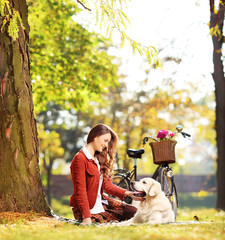 Beautiful female sitting on grass and looking at her dog