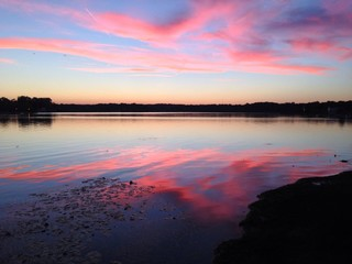 Pink clouds reflected on lake