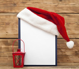 Santa hat on clipboard with blank sheet of paper for your text