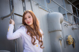 Pretty woman sailor posing with steel ladder on battleship