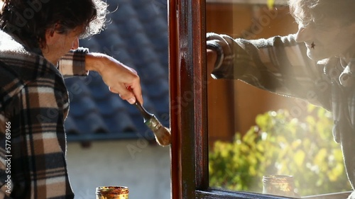 maintenance worker painting wooden window