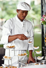 Asian chef laying a table with luxury food and drinks on wedding