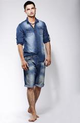 Modern Barefoot Man in Blue Jeans posing