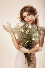Simplicity. Elegant Woman with Bouquet of Flowers posing