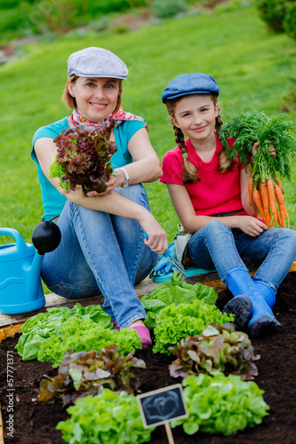 Gardening, girl with mother working in vegetable garden