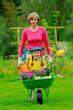 Gardening, girl in barrow helping mother in the garden