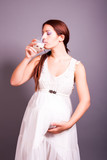 pregnant woman drinking a glass of milk