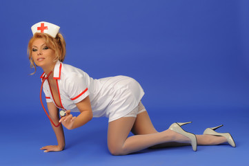 Sexual woman in nurse suit with stethoscope blue background..Sto