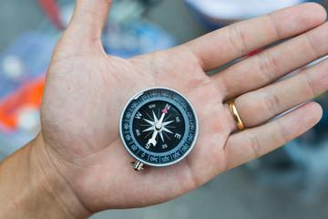 Metal compass on bare hand