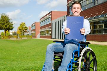 junger Rollstuhlfahrer zeigt Bewerbung
