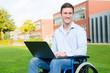 Mann mit Notebook im Rollstuhl
