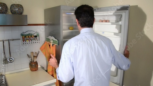 disappointed man looking in his empty fridge