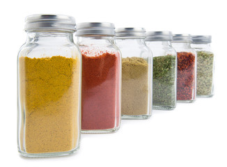 Set of assorted colorful powder spices in glass bottle isolated