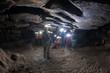 People exploring dark cave. Grotta del Farneto, Bologna, Italy.