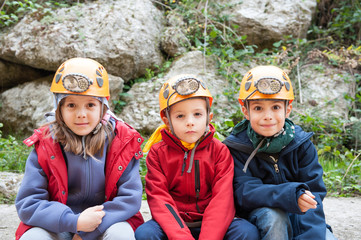 Group of young kids wearing helmet for cave exploration.