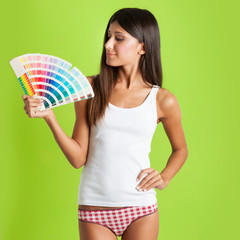 Beautiful girl showing colors palette against colorful green bac