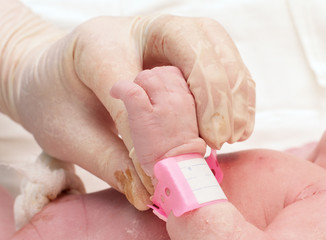 doctor holding the hand of a newborn baby