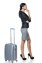 Side view of  pensive woman in full length with suitcase