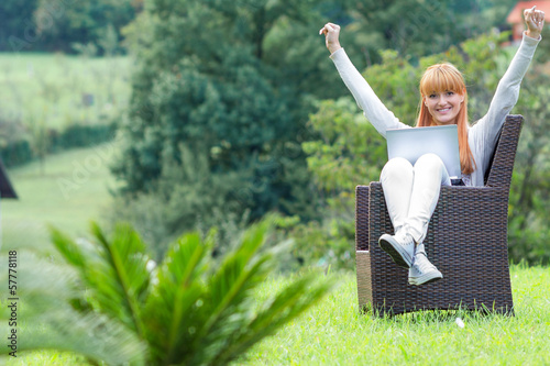 Girl sitting with laptop, arms raised, outdoor