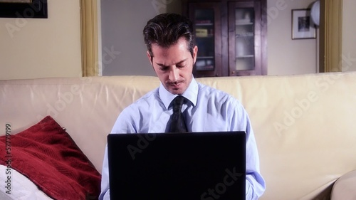 businessman working at laptop in living room