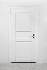 Classical closed wooden door in white office wall