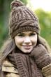 Portrait d'une jolie brune souriante avec un bonnet marron