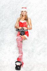Sexy blonde fitness model with kettlebell in snowflakes