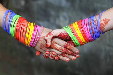 Shaking hands decorated with colorful bracelets and henna tattoo