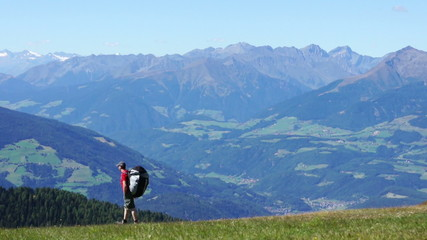 Paraglider with backpack walking on the top of the mountains